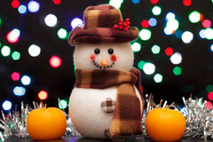Christmas snowman with orange candles  on a black background Royalty Free Stock Images