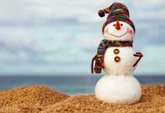 Christmas snowman in red santa hat and sunglasses at sunny beach royalty free stock photography