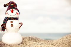 Christmas snowman in red santa hat and sunglasses at sunny beach. Holiday concept for New Years Cards. Stock Photo