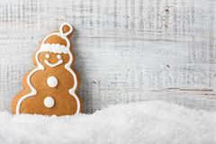 Christmas snowman-shaped cookie gingerbread on the snow Royalty Free Stock Images
