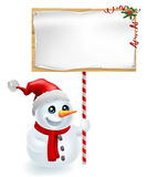 Christmas Snowman and Sign. A cute Christmas snowman with Santa hat holding a Christmas sign Stock Image
