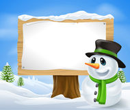 Christmas Snowman Sign. Christmas Snowman and large wooden Christmas sign with copyspace Stock Images