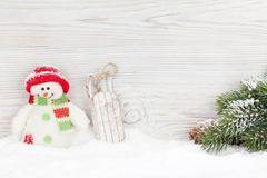 Christmas snowman and sledge toys and fir tree branch. View with copy space Royalty Free Stock Photography