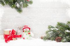 Christmas snowman and sledge toys, gift and fir tree. Christmas snowman and sledge toys, gift box and fir tree branch. Xmas backdrop with copy space Royalty Free Stock Images