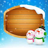 Christmas snowman and snowgirl with blank wooden sign vector  Royalty Free Stock Photo