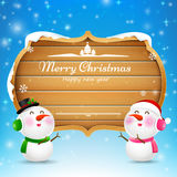 Christmas snowman and snowgirl wooden sign with text merry chris Royalty Free Stock Photography