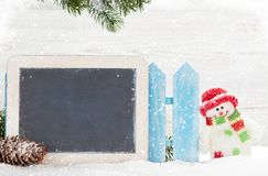 Christmas snowman toy and chalkboard. Christmas snowman toy and xmas fir tree branch. With chalkboard for your greetings Royalty Free Stock Photography
