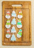 Christmas snowman and tree cookies on the cutting board winter selebration background. Stock Photos