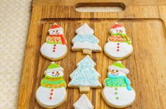 Christmas snowman and tree cookies on the cutting board winter selebration background. Christmas snowman and tree cookies on the cutting board winter Stock Image