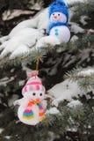 Christmas Snowmen Christmas tree. Bright cheerful Christmas Snowmen on a snowy tree lie Stock Images