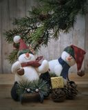 Christmas Snowmen. A couple of snowmen Christmas ornaments playing beneath the Christmas tree royalty free stock photography