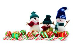 Christmas snowmen. Cute toy snowmen with Christmas baubles and candy canes over white Royalty Free Stock Images