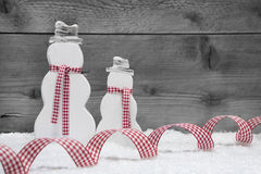 Christmas snowmen with snow and ribbon on grey wooden background Stock Images