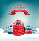 Christmas snowy background with a red sack with gift boxes. Stock Photography