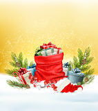 Christmas snowy background with a red sack with gift boxes. Royalty Free Stock Images