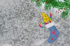 Christmas sock with gifts on green natural fir branch on a background of grey with white patterns of the metal Stock Images