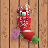 Christmas sock with gifts suspended on the wood wall Stock Images
