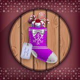 Christmas sock with gifts suspended on the wooden circle board Royalty Free Stock Photo