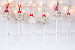 Christmas soft home craft decorations and burning lights on a wood white  background. Stock Photos