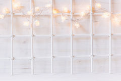 Christmas soft home decor with lights burning on a white wooden background.