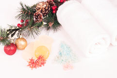 Christmas spa getaway with bath salts, soaps and bath salts close-up. Christmas spa getaway concept on a bed with baubles, soaps, bath salts and towels close-up Royalty Free Stock Photos