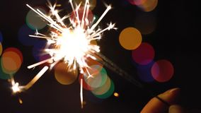 Christmas sparkler burning on a background of christmas tree with colorful bokeh and christmas lights stock footage