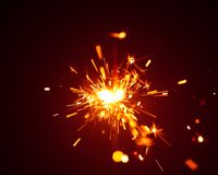 Christmas sparkler in haze with red light Royalty Free Stock Images