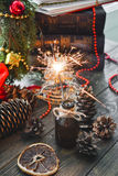 Christmas sparklers. Christmas sparklers on a background of old books, cones and Christmas wreaths Royalty Free Stock Image