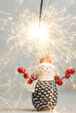 Christmas. Sparklers. Snowman. Gifts. Christmas. Xmas. A snowman holding a sparklers on the background of gifts Stock Photo