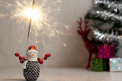 Christmas. Sparklers. Snowman. Gifts. Christmas. Xmas. A snowman holding a sparklers on the background of gifts Stock Images