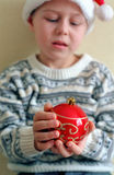 Christmas sphere in child hands Stock Image