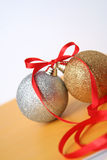 Christmas spheres. Christmas. New Year's spheres lie on a yellow background with a red tape Royalty Free Stock Images