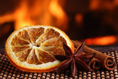 Christmas spices 2. Orange slice with anis and cinamon sticks on bamboo mat in front of fireplace royalty free stock photos