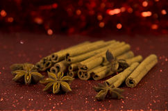 Christmas spices. Anise and cinnamon on a red shiny background Stock Photography