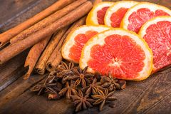 Fresh orange, cinnamon sticks and star anise on dark wood background Royalty Free Stock Images