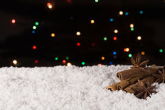 Christmas spices on the snow with lights on the background. Copy space Stock Photography