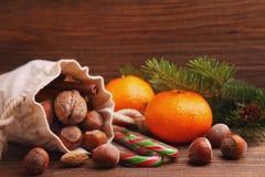 Christmas spirit: nuts, tangerines, Christmas tree, nuts, a flashligh Stock Photo
