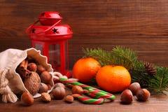 Christmas spirit: nuts, tangerines, Christmas tree, nuts, a flashligh Stock Photos