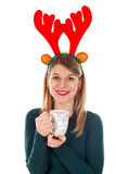 Christmas spirit. Picture of a smiling young woman with raindeer slide holding a cup of tea Stock Images