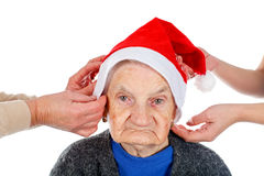 Christmas spirit. Portrait of an elderly woman wearing Santa`s hat on an isolated background Royalty Free Stock Photography