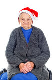 Christmas spirit. Portrait of an elderly woman wearing Santa`s hat on an isolated background Stock Images