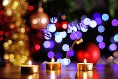 Christmas spirit scene with golden candles and glittering tree and baubles. Christmas spirit scene with golden candles and glittering tree lights and baubles in royalty free stock photo