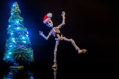 Christmas Spirit. A skeleton dancing around a Christmas Tree with lights stock photo