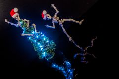 Christmas Spirit. A skeleton dancing around a Christmas Tree with lights royalty free stock images