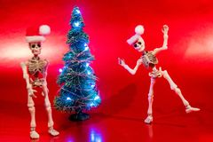 Christmas Spirit. Skeletons dancing around a Christmas Tree with lights stock images