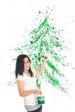 Christmas Splatter. An attractive preteen flinging green paint to create a splattered Christmas tree image behind her.  On a white background Stock Photos