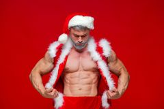 Christmas. Sport, activity. Sexy Santa Claus . Young muscular man wearing Santa Claus hat demonstrate his muscles Stock Photography