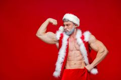 Christmas. Sport, activity. Santa Claus . Young muscular man wearing Santa Claus hat demonstrate his muscles Royalty Free Stock Photography