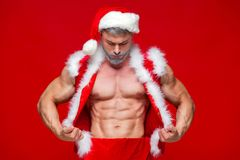 Christmas. Sport, activity. Santa Claus . Young muscular man wearing Santa Claus hat demonstrate his muscles Royalty Free Stock Images