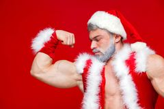 Christmas. Sport, activity. Santa Claus . Young muscular man wearing Santa Claus hat demonstrate his muscles Royalty Free Stock Photo